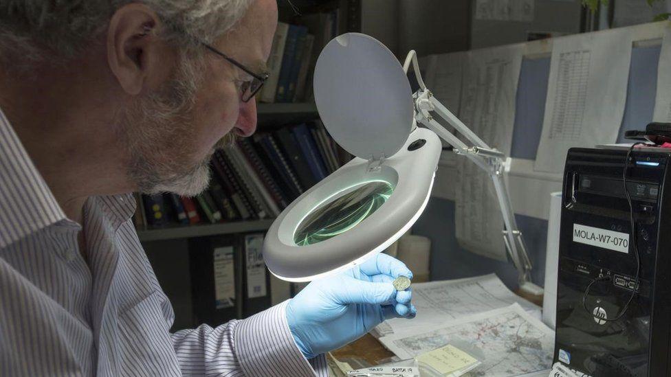 Dr Julian Bowsher examining coin