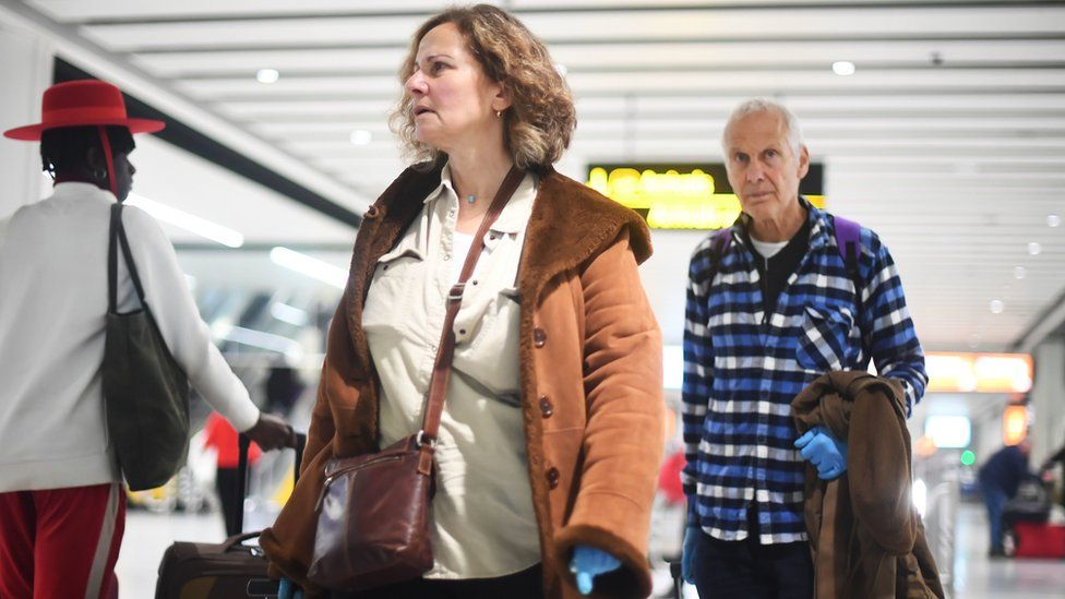 A couple walking through Gatwick Airport wearing latex gloves
