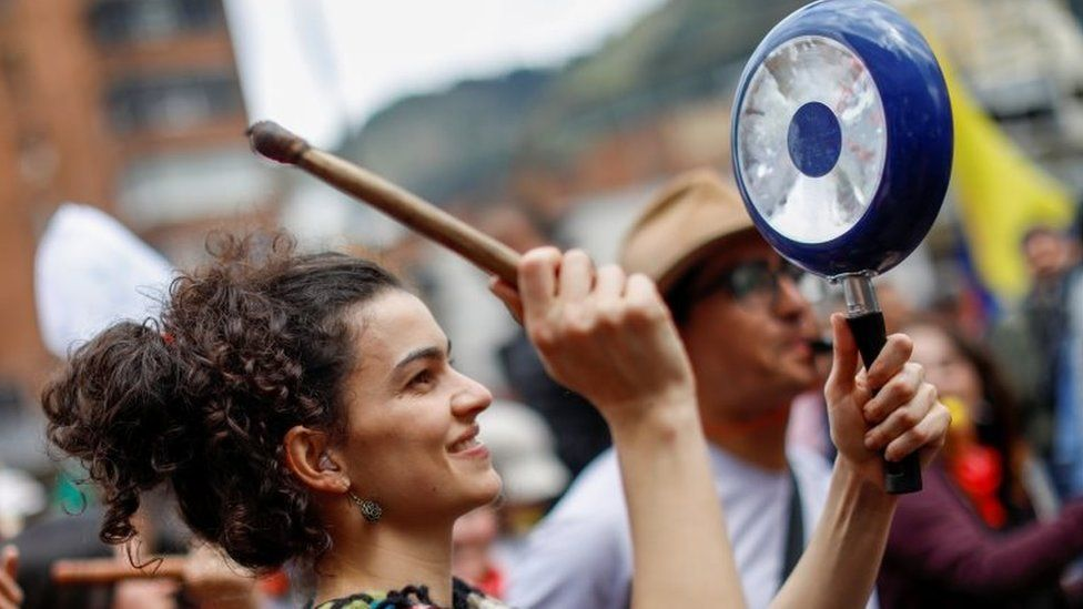 A woman hits a pan during a protest in Bogota on 27 November 2019