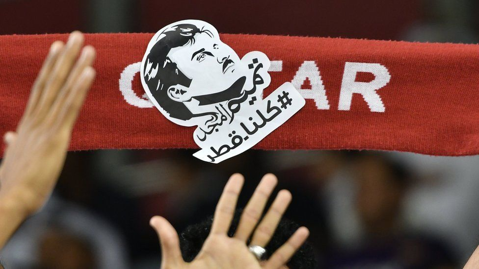 """Qatari football fans hold picture of Emir Sheikh Tamim bin Hamad Al Thani saying: """"All of us are Qatar"""" at a football match in Doha (13 June 2017)"""