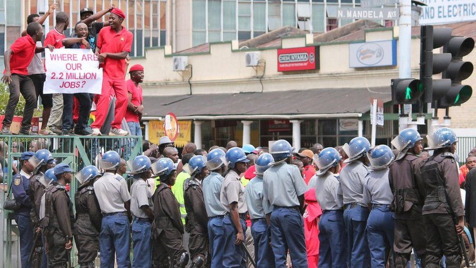 Zimbabwean police officers keep an eye on opposition party supporters as they prepare to march during a protest aimed at President Robert Mugabe in Harare, Zimbabwe, Thursday, March, 14, 2016