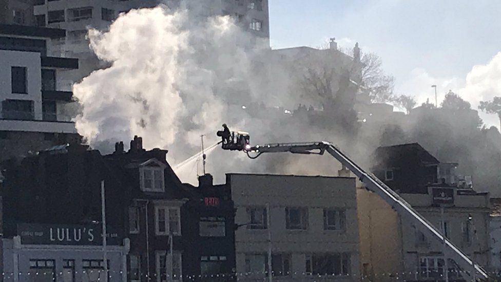 Fireman uses turntable ladder to reach the fire