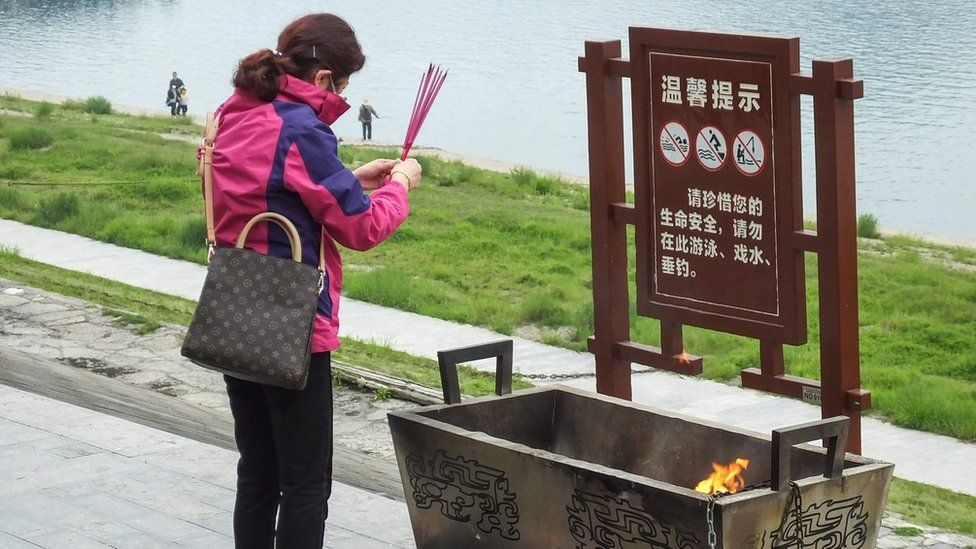 A woman burns incense ahead of the tomb sweeping festival