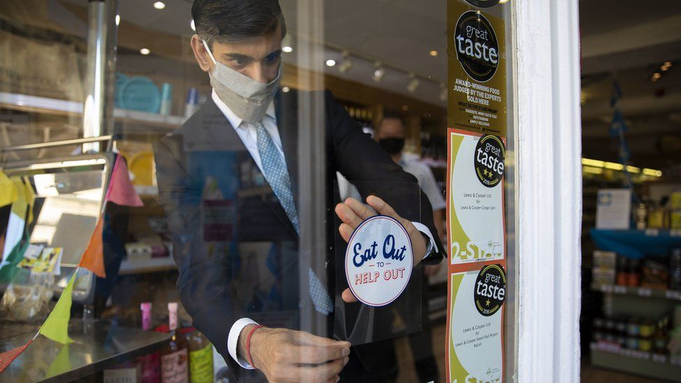 Chancellor Rishi Sunak places a sticker promoting the scheme on a window