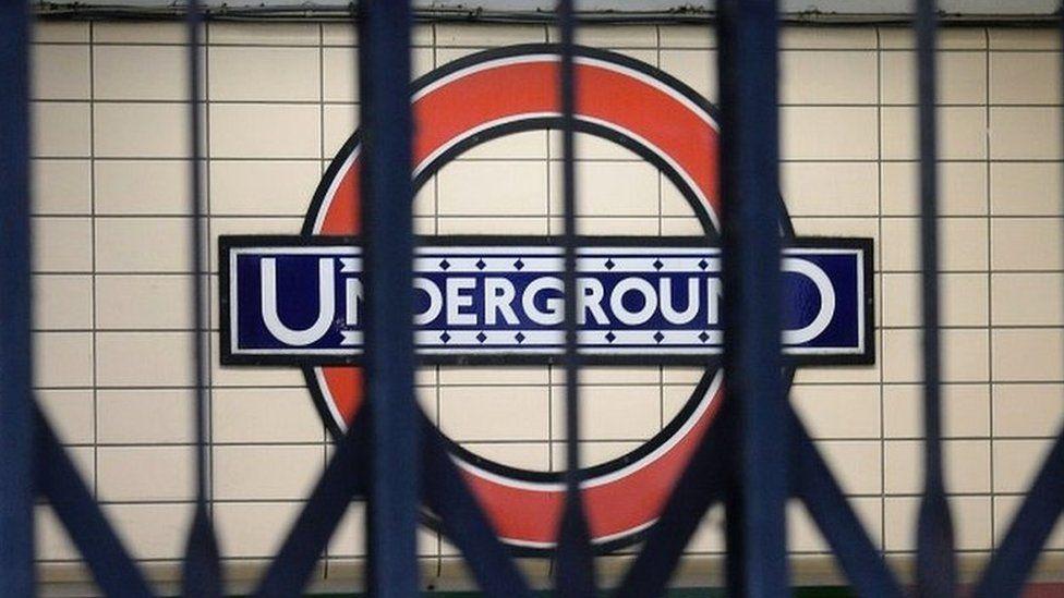 London Underground sign behind closed gates
