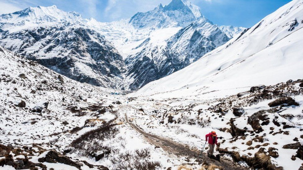 A trekker walks to the Annapurna base camp with Mount Machapuchare in the background