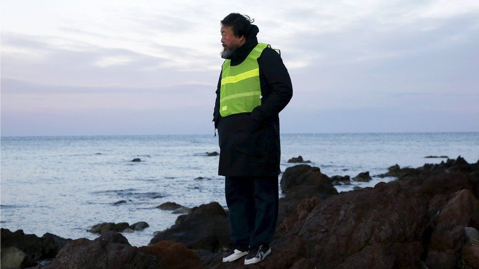 Ai Weiwei in a high vis jacket, standing on a rocky outcrop
