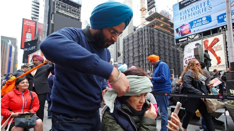 Sikh man ties turban on a woman in New York City
