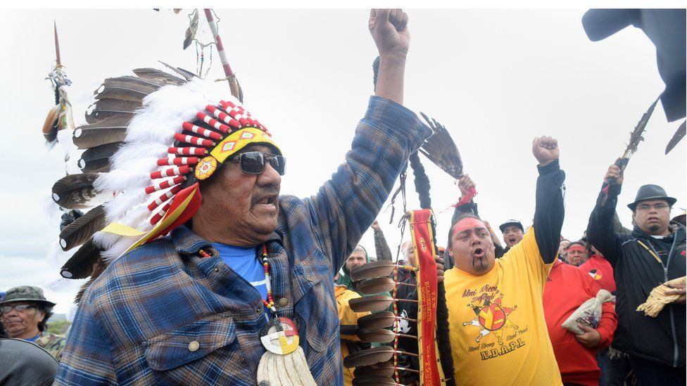JR American Horse, left, raises his fist with others while leading a march to the Dakota Access Pipeline site in southern Morton County North Dakota on 9 September 2016