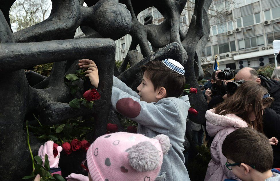 A child lays roses at the Holocaust Memorial monument in Thessaloniki