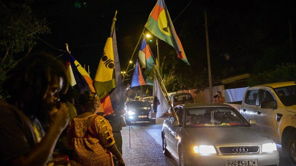 "Activists display their flags in front of the pro-independent Union Caledonienne (UC) following the referendum on New Caledonia""s independence on November 4"
