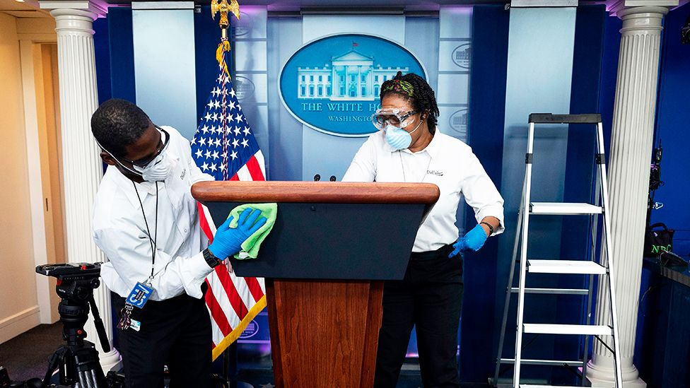 Cleaning staff disinfect the lectern in the White House Press Briefing Room - 9 April 2020