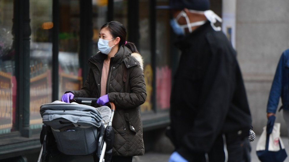 People wear face masks in New York, the epicentre of the US outbreak
