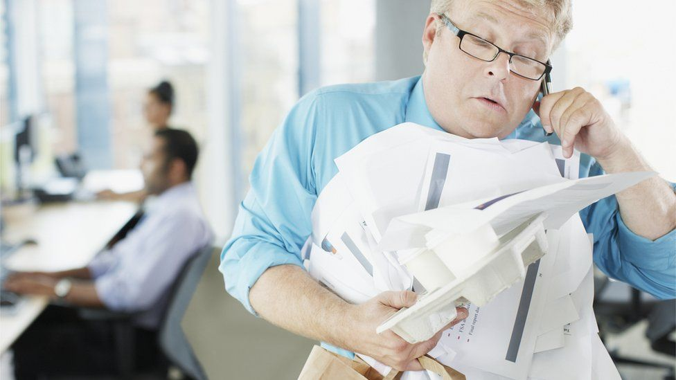 Businessman carry messy sheaf of papers