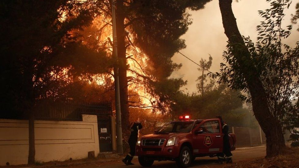 Firefighters at work to extinguish a wildfire in the area of Stamata