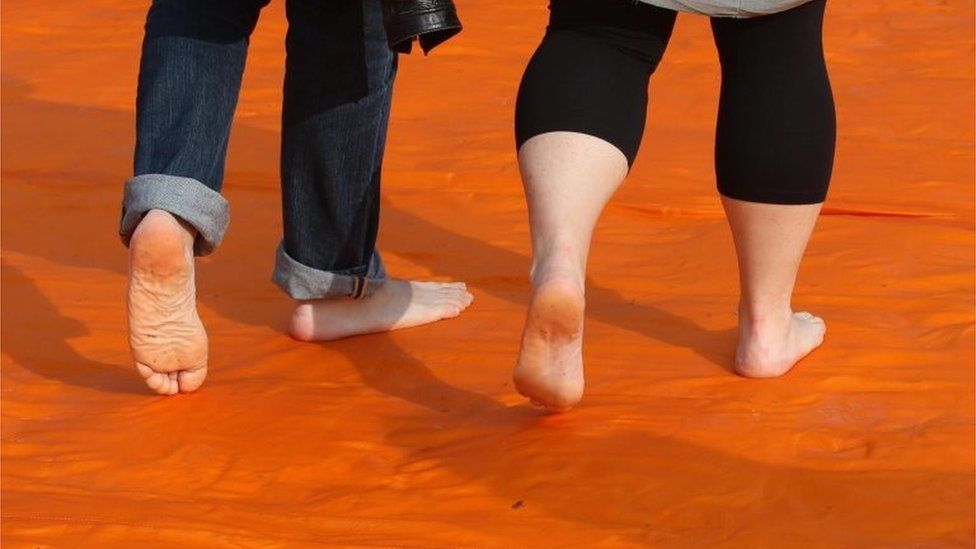People take their shoes off to walk on the Floating Piers installation by artist Christo 18/06/2016
