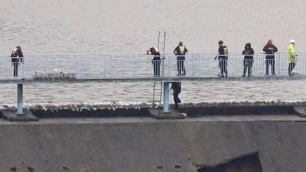 Workers put sandbags on reservoir edge