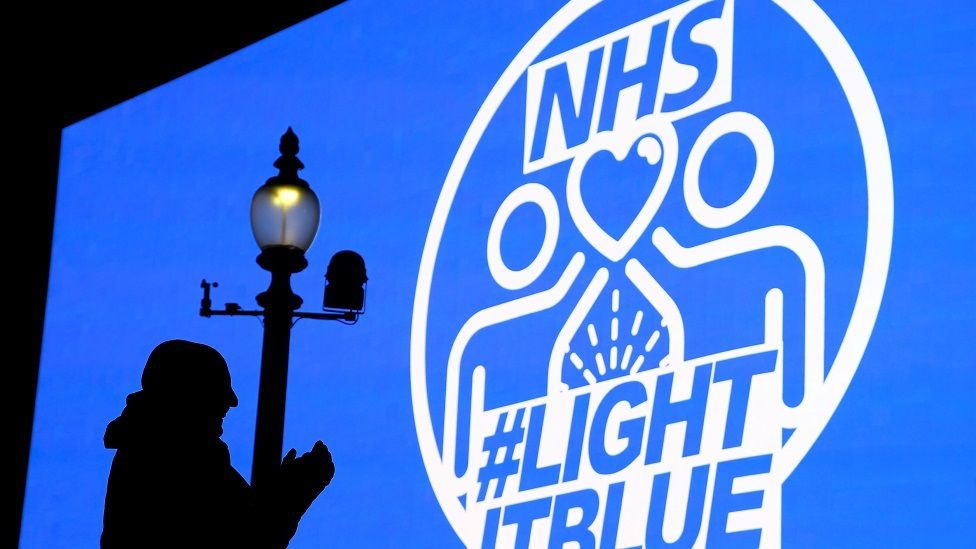 A person is seen in silhouette, applauding the work of the NHS, in front of big screen in Piccadilly Circus