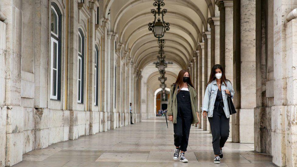 Two women wearing face masks walk in Lisbon, Portugal