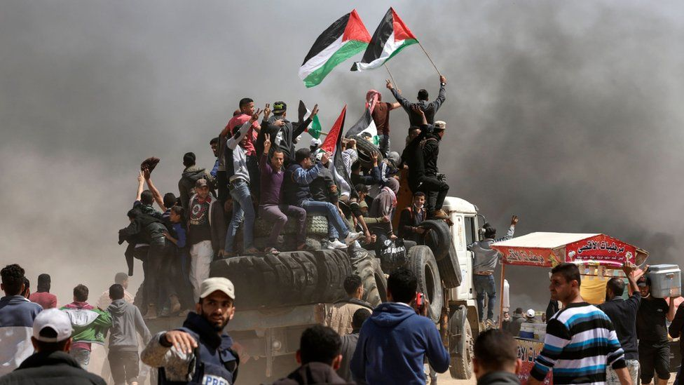 Palestinian men wave flags during a protest east of Gaza City on 6 April 2018