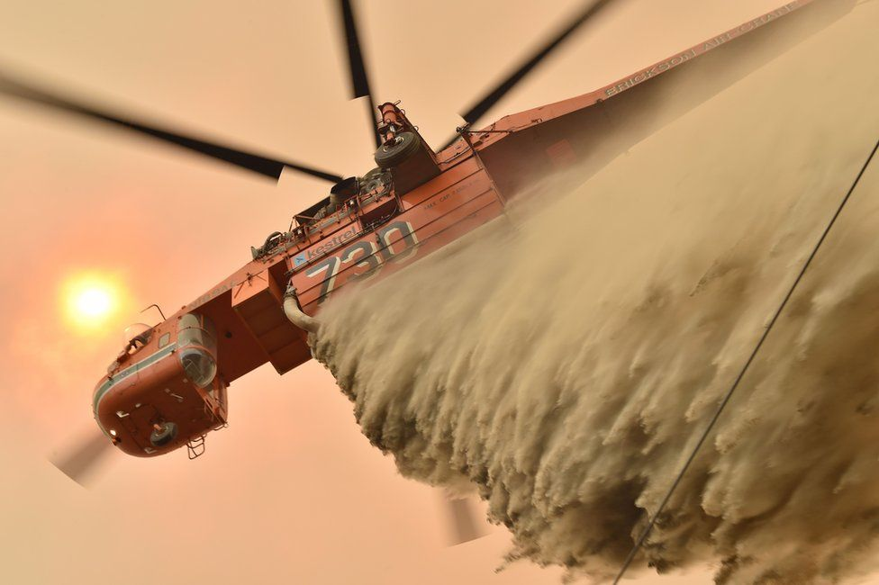 A helicopter drops fire retardant on the ground