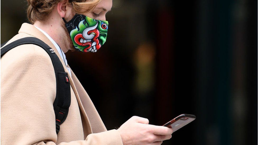 Woman looking at her phone and wearing a mask