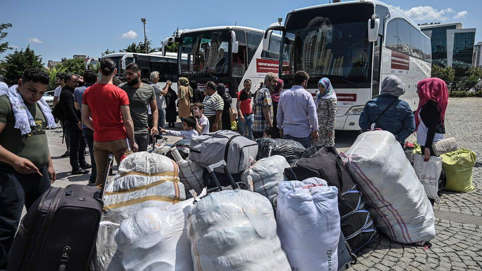 Syrian refugee families wait with other volunteers to board buses returning to neighbouring Syria in the Esenyurt district of Istanbul