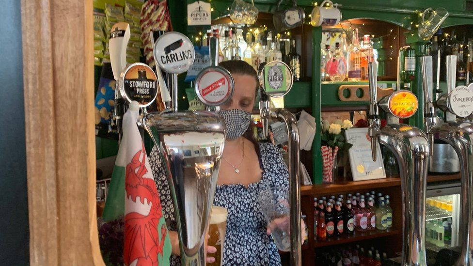 Woman wearing mask serving drinks behind the bar of The Landsdowne pub in Cardiff