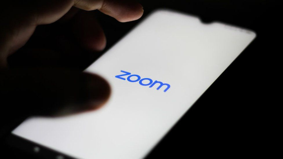 The Zoom logo is shown on a smartphone in close-up with a hand hovering nearby