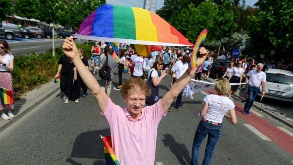 A man waves a flag at a gay pride event in Poland, 2019