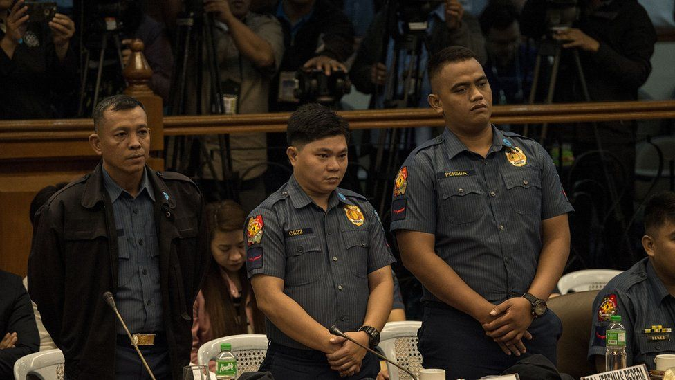 Philippine police officers Arnel Oares, Jerwin Cruz, and Jeremias Pereda, accused of killing 17-year-old student Kian Delos Santos during an anti-drug raid, stand during a Senate hearing in Manila on September 5, 2017.