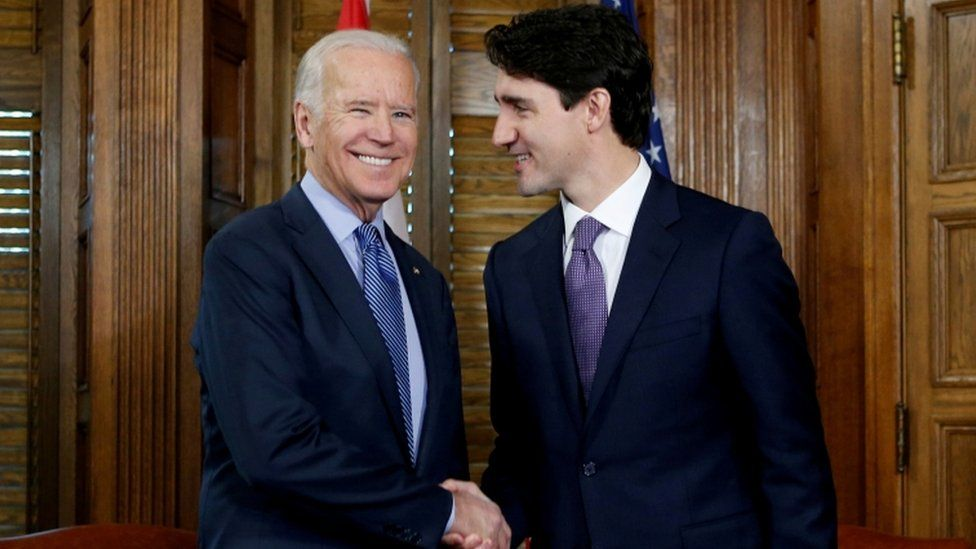 Canada's Prime Minister Justin Trudeau (R) shakes hands with US Vice President Joe Biden