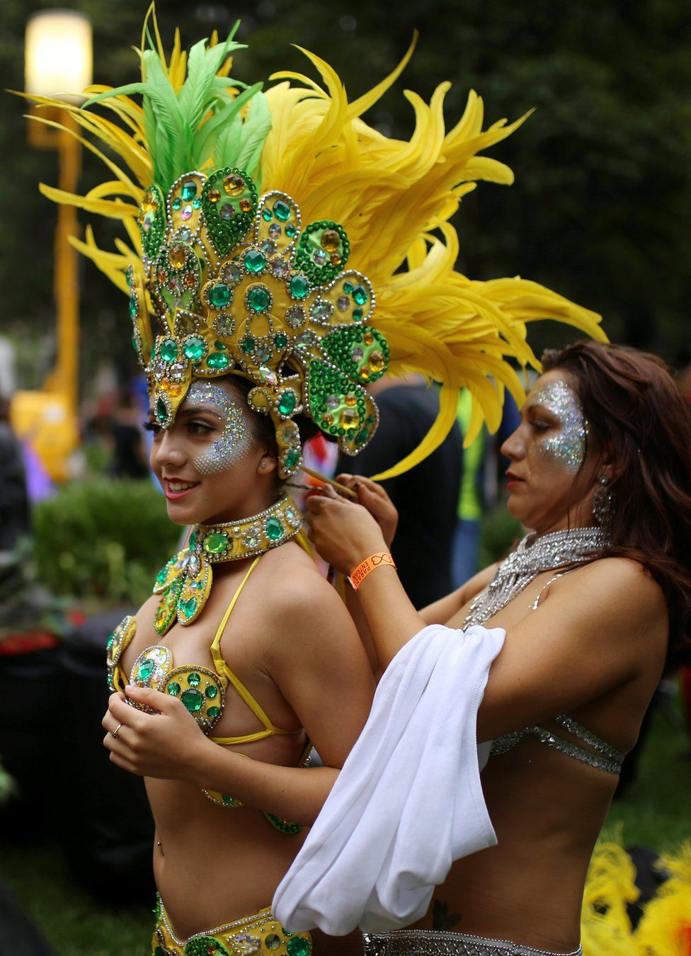 A woman in a bikini and elaborate yellow and green feathered headress and collar, in the annual Sydney Gay and Lesbian Mardi Gras festival prepares her costume in Sydney, Australia March 4, 2017