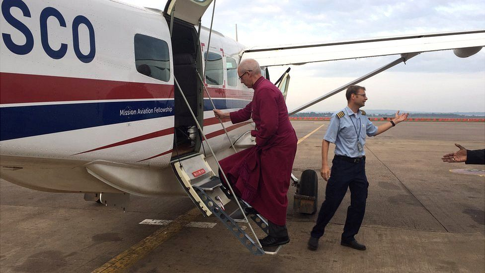 Justin Welby embarks on an aircraft in Uganda