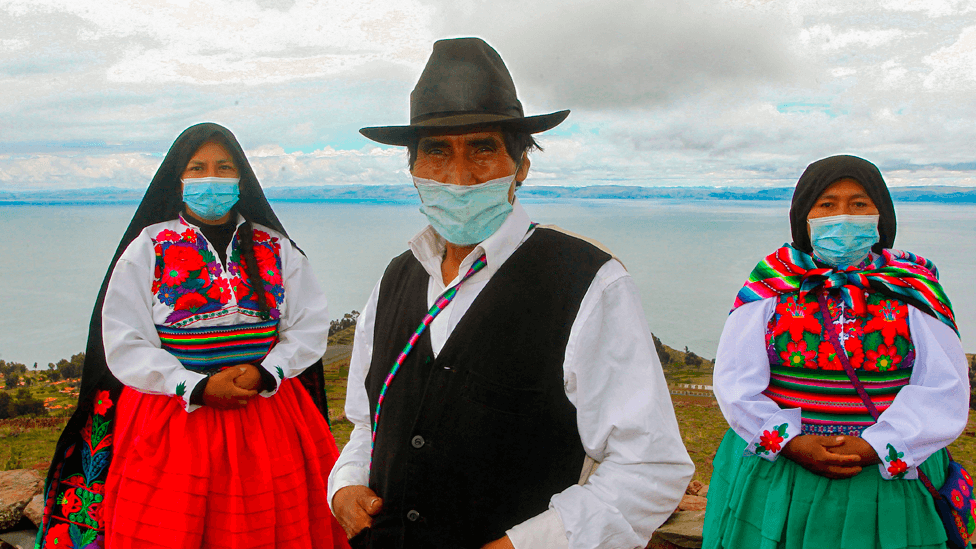 Aymara people from Puno, Peru, wearing masks against Covid-19 participate in a traditional ceremony paying tribute to Mother Earth, Pachamama in Aymara, on a slope of the on the Pachatata hill in the Aimantani Island in Lake Titicaca sitting above 4,000 meters (13,000 feet) above sea level on the border with Bolivia on January 21.