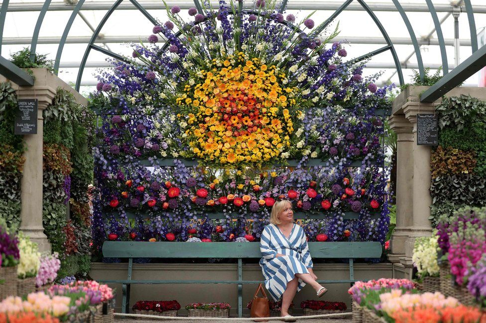 A visitor sits beneath a display of flowers at the floral market at the 2018 Chelsea Flower Show in London on May 21, 2018