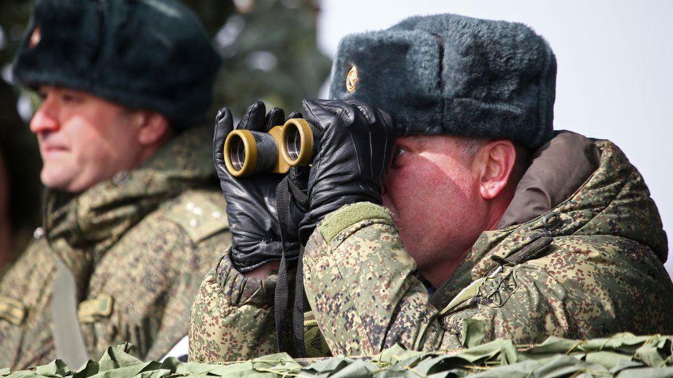 Русский солдат смотрит в бинокль