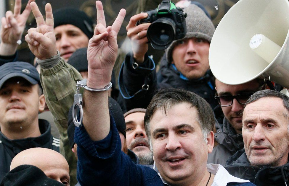 Georgian former President Mikheil Saakashvili flashes a victory sign after he was freed by his supporters in Kiev