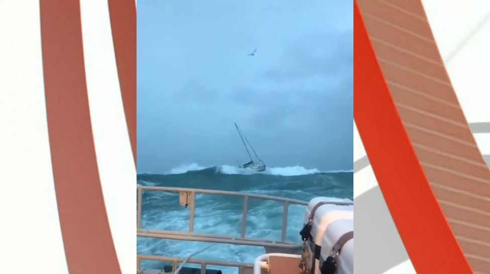 Yacht being towed by lifeboat in rough seas