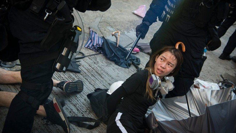 Estudiante arrestada en el suelo en Hong Kong.