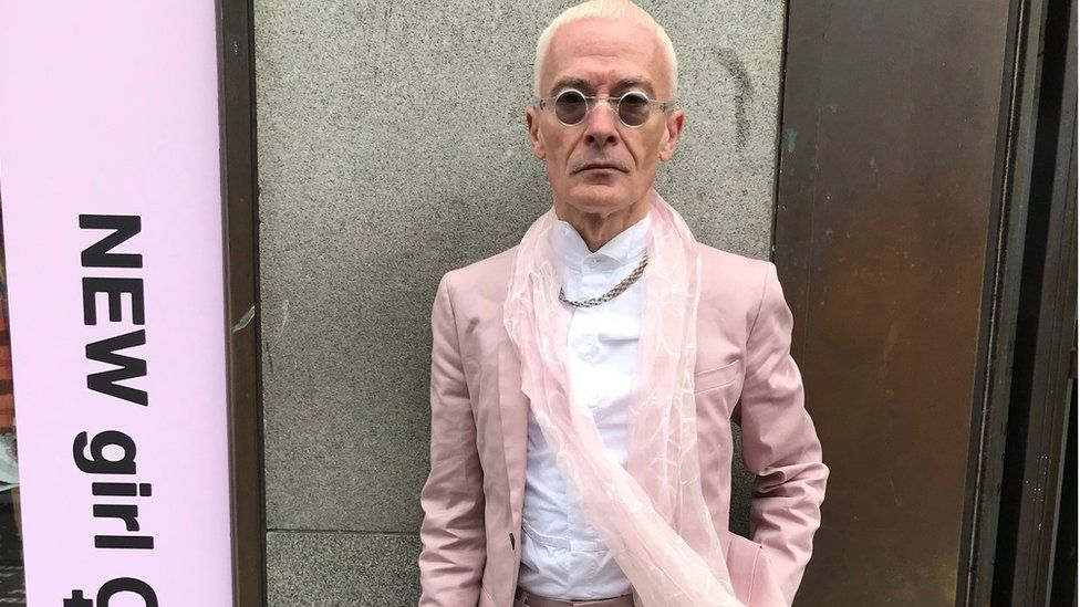 Actor Matthew Sim wearing a rose gold suit and matching accessories