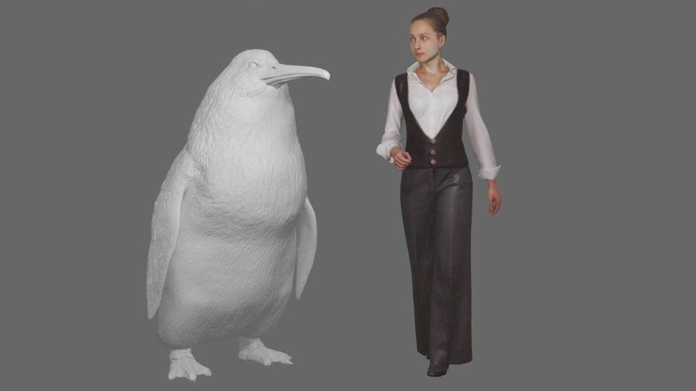 A model of the penguin standing next to a woman for scale