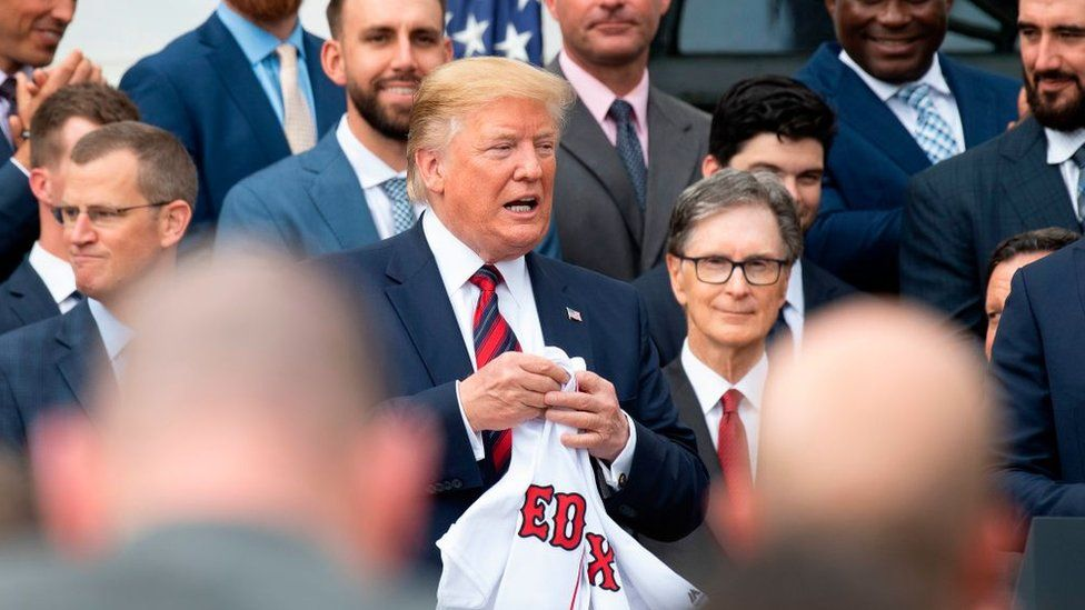US President Donald Trump (C) holds a Boston Redsox's jersey that was given to him as he welcomed the 2018 World Series Champions to the White House in Washington, DC, 9 May 2019