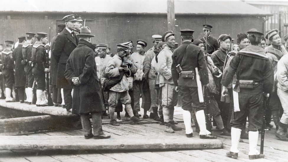 Japanese troops with captured Chinese men and boys in then Shangdong, China