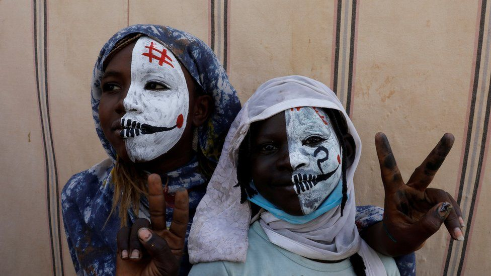 Sudanese girls with half painted faces make victory signs as they watch protesters demonstrating