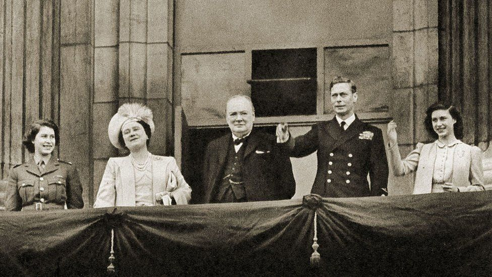 Wartime Prime Minister Winston Churchill stands on the balcony of Buckingham Palace alongside the Royal Family (with the Queen, then Princess Elizabeth, on the left) on VE Day, 8 May 1945