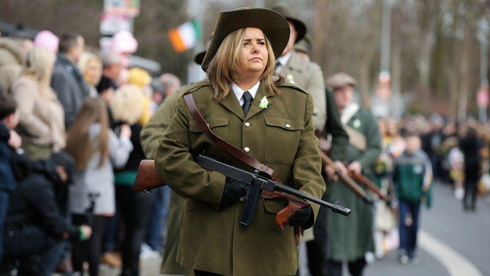 woman walks with rifle