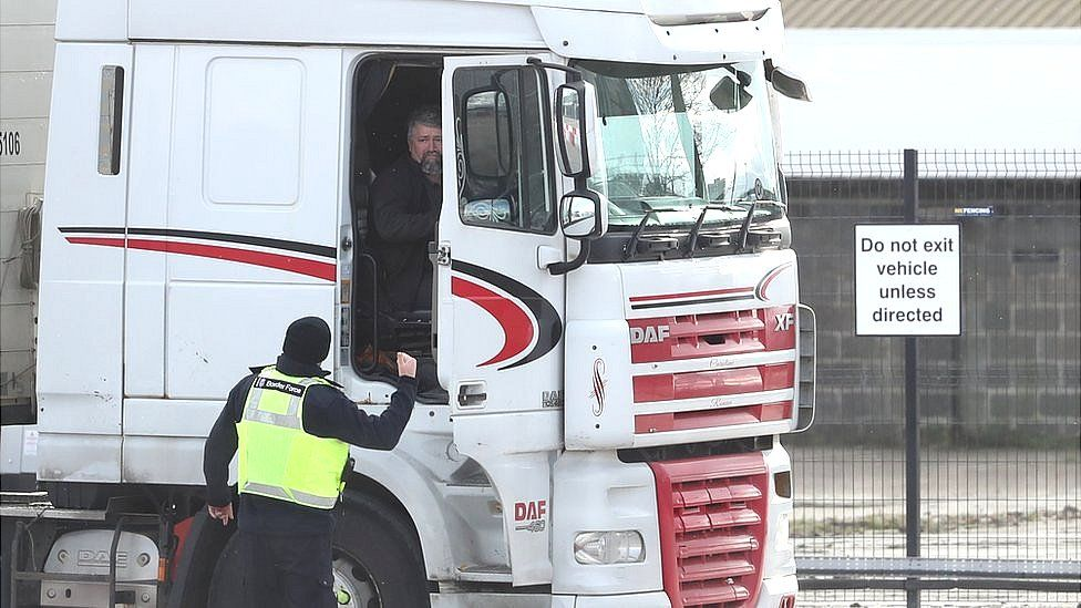 A Border Force officer talks to a lorry driver at the Department of Agricultural, Environment and Rural Affairs facility on Duncrue Street near Belfast Harbour, as post-Brexit checks at all Northern Ireland's ports resume.