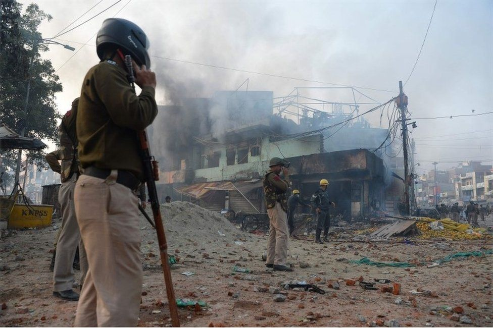 Policemen stand along a road scattered with stones as smoke billows from buildings following clashes between supporters and opponents of a new citizenship law, at Bhajanpura area of New Delhi on February 24, 2020