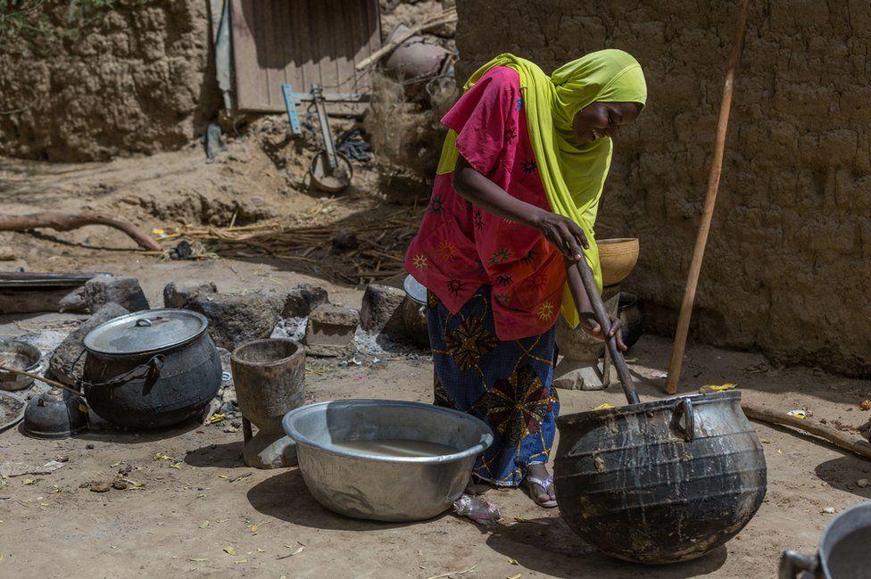 Fadouralaye Massaoudou stirs a pot in Norandé